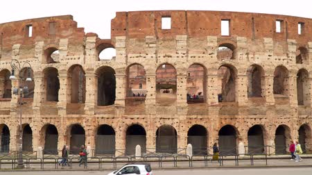 colosseo : Rome, Italy - March 19, 2018: Tourists and cars against the backdrop of the Coliseum in Rome
