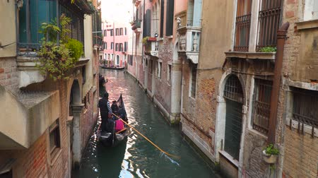 small vessels : Venice, Italy - March 23, 2018: Gondolas swim through the narrow canals of Venice Stock Footage
