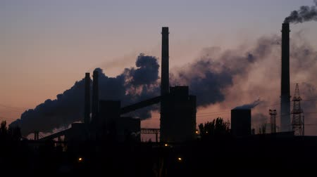 dioxid : Pipes and smoke of the metallurgical plant against the background of the pre-dawn sky. Stock mozgókép
