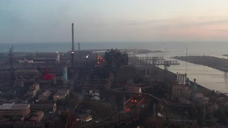 metalurgia : Aerial view. Industrial production plant with blast furnaces by the sea. Evening time
