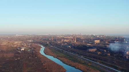 combinado : Industrial enterprise on the river bank in the city. Evening time. . Aerial view