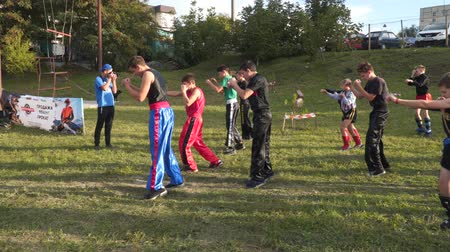 каратэ : MARIUPOL, UKRAINE - SEPTEMBER 29, 2018: Trainer with young athletes are training outdoors. With the free input.