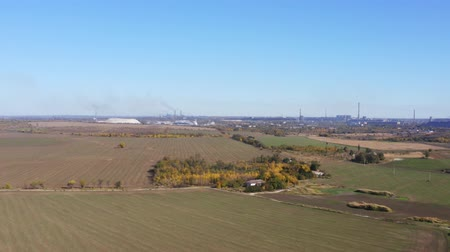 metallurgical plant : Aerial video. Farm among the autumn fields. On the horizon metallurgical plant