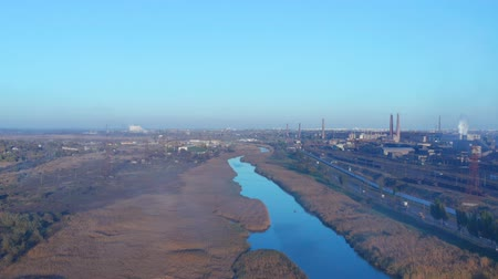 zarostlý : Aerial video. The river near the industrial enterprise. Evening in the fall