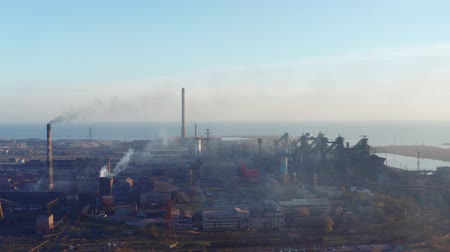 metallurgic : Aerial video. Blast furnaces of a metallurgical plant on the seashore. Pollution of the environment. Evening time