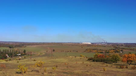 metallurgical plant : Autumn fields and steel plant against the blue sky. Aerial video. Stock Footage