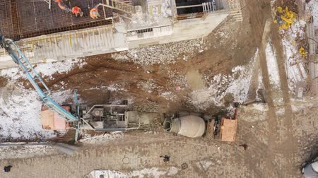 peoples : Aerial view. Auto Concrete Mixer and Concrete Feeding Concrete at Construction Site. Peoples faces are not visible