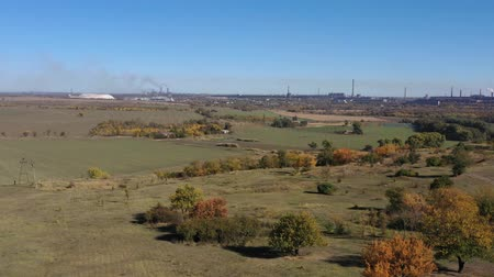 harvesting : Aerial view of the autumn fields. On the horizon of a metallurgical plant.