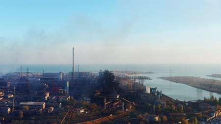 emise : Metallurgical plant on the seashore. Shot from a birds eye view. Evening time
