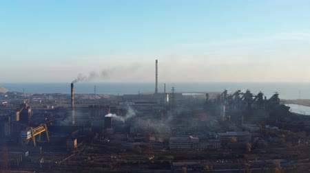 vapor : Blast furnaces by the sea. Shot from a birds eye view. Evening time Stock Footage
