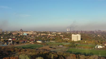put : Aerial view. Residential area in the city at sunset in the fall. Autumn trees, football field Vidéos Libres De Droits