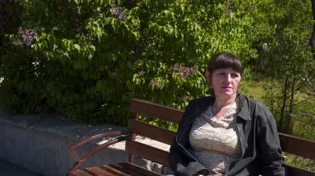 leylak : A young woman sits on a bench. In the background is a blooming lilac Stok Video