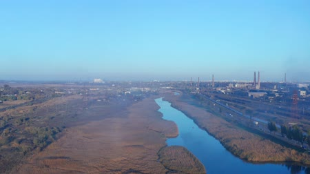 metallurgic : River overgrown with reeds near the metallurgical plant. Aerial view. Evening time. Smog