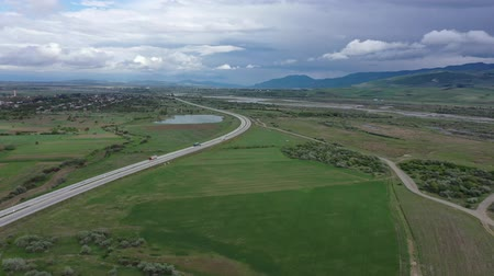orta hava : Freeway among green fields. Mountains are visible on the horizon. Cloudy sky Aerial video
