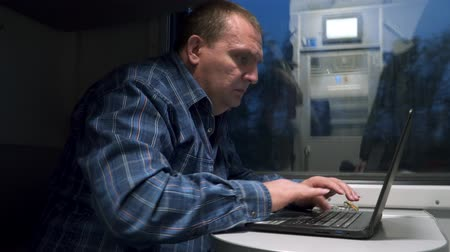 train workers : A man in a train car works with a laptop. Freelancer on the train Stock Footage