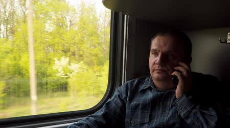 train workers : A man emotionally near the window of a moving train communicates by phone. Stock Footage