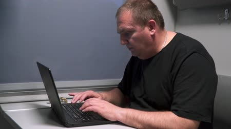 train workers : A man near the window of a moving train with a laptop. Stock Footage