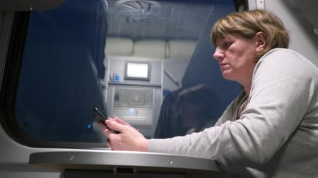 Woman with a phone near the window in a moving train.