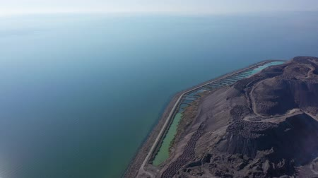 Slag mountain of a metallurgical plant on the seashore. Environmental pollution. Aerial view