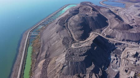Slag mountain on the seashore. Pollution. Smog in the city. Aerial view