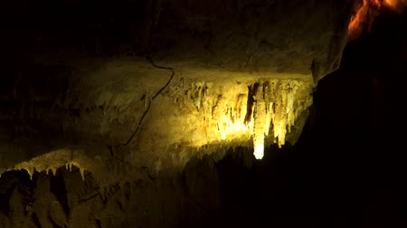 geológiai : Dimly lit cave and stalactite hanging from the cave ceiling.