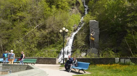 Borjomi, Georgia - May 7, 2019: Tourists near the monument to Prometheus in the city of Borjomi. Tourists sit on a bench and drink mineral water