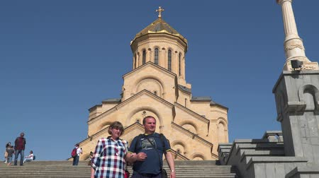 Tbilisi, Georgia - May 8, 2019: Tourists on the background Tsminda Sameba Cathedral. Holy Trinity Cathedral of Tbilisi Georgia.