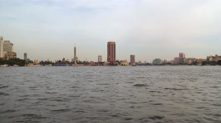 nílus : Cairo, Egypt - January 14, 2020: View from a floating boat on buildings located on the banks of the Nile River. Stock mozgókép