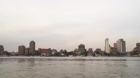 Cairo, Egypt - January 14, 2020: Buildings on the banks of the Nile in Cairo. View from a floating boat. Overcast sky 動画素材
