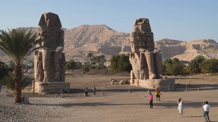 hieroglifa : Luxor, Egypt - January 16, 2020: The Colossi of Memnon are two massive stone statues of the Pharaoh Amenhotep III