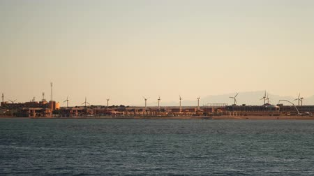 Wind turbines on the coast. View from the sea from the ship. Evening time Stock Footage