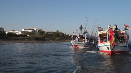 motorbot : Luxor, Egypt - January 16, 2020: Tourists in boats sail on the Nile River. Luxor city