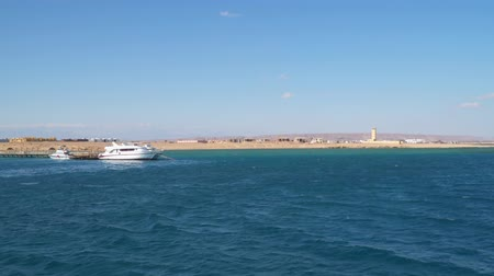 White yacht and motor boat at the pier. Shore of the Red Sea in Egypt. View from the sea