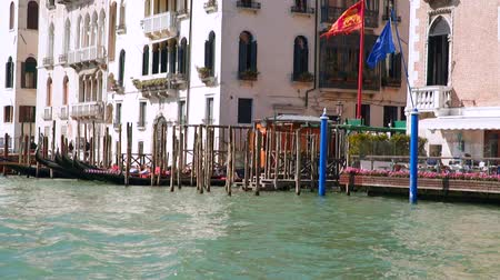 venezia : Venice, Italy - March 23, 2018: Gondolas at the pier and buildings near canals. View from a floating boat. Slow motion Stock Footage