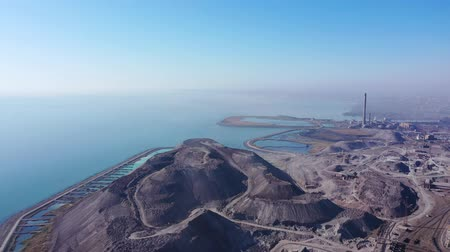taş ocağı : Slag mountain on the seashore. Environmental pollution. On the horizon a city in the fog. Aerial view