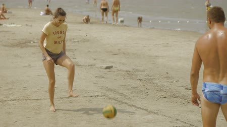 volleyball : Girl is playing football with her boyfriend on the beach
