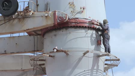 leisureactivity : The sailor on the ship fulfills his duties. the employee is engaged in servicing. man paints a mast. male colors part of the vessel