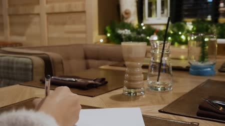 caffe : Girl writing on paper in winter. Woman inspire at night in the caffe. Writer begins to write new book in the restaurant
