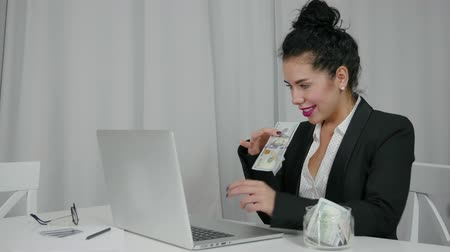pago : Businesswoman earns money online and winks. Woman pulls US dollars out of her laptop. Lady in a business suit. Trader, freelancer or successful entrepreneur. Concept of abundance