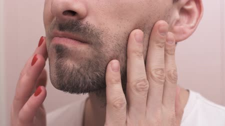 tıraş : Male and female hands touch the face after shaving. Half-shaved man gets into the frame. The concept of choice and upbringing in society. Shave or not shave Stok Video