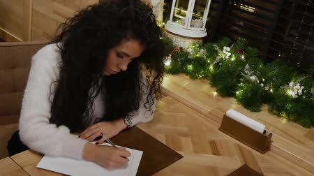 unalom : Beautiful girl with curly hair is writing a poem in a restaurant. Cute brunette writer in a white sweater creates novel at winter cafe