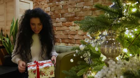 dát : Beautiful curly-hair girl gives a gift near New Year tree. Cute brunette in a white sweater stretches a beautiful box Dostupné videozáznamy