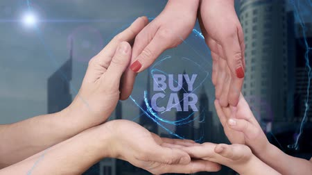 árverés : Mens, womens and childrens hands show a hologram Buy car. The family holds a magical inscription on the background of a modern city