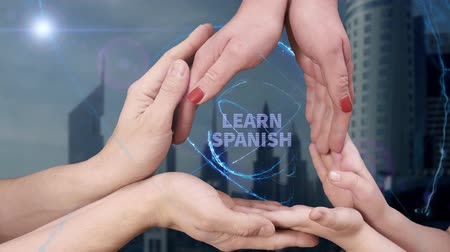 multilingual : Mens, womens and childrens hands show a hologram Learn Spanish. The family holds a magical inscription on the background of a modern city