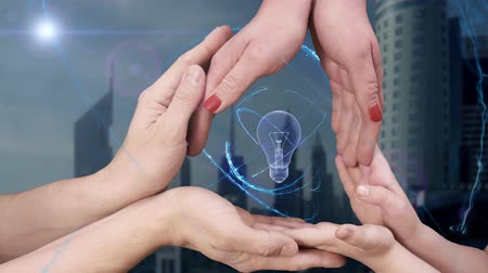 holographic : Mens, womens and childrens hands show a hologram 3D bulb. The family holds a magical inscription on the background of a modern city
