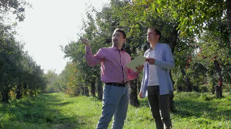 two rows : Two farmers preparing to conclude an agreement in the apple orchard. A pair of rural businessmen sign papers on a background of green trees