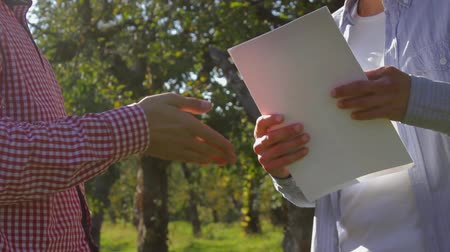 two rows : Two unrecognizable farmers shake hands and preparing to conclude an agreement on a background of green trees. A pair of rural businessmen in the apple orchard