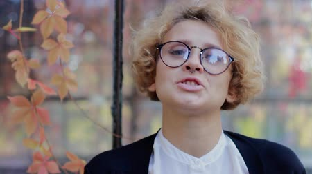 ukłon : Beautiful happy blond woman with glasses looking at camera and nods approvingly. Young business woman with curly hair and blue eyes on a background of autumn leaves