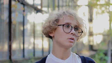 odmítnutí : Offended blonde woman with glasses sadly looks at the camera. Young business woman with curly hair and blue eyes shows emotion