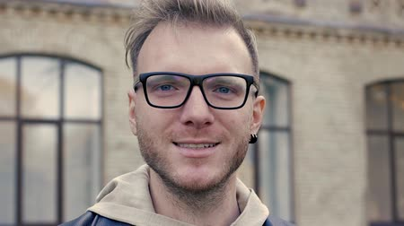 duše : Emotional video-portrait of a nice guy. A blue-eyed man with glasses smiles and looks into the frame. Young businessman or student on the background of the university